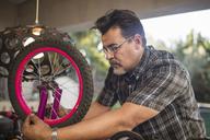 Man fixing wheel of children's bicycle - ZEF15907