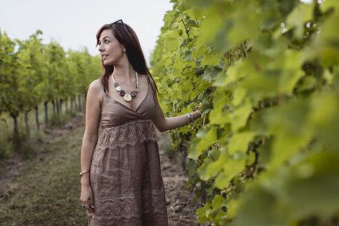 Woman standing in vineyard, wearing summer dress - MAUF01602