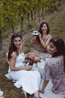 Friends having picnic in a vineyard, one woman taking pictures with instant camera - MAUF01623