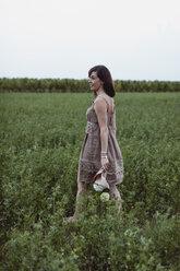 Woman wearing summer dress, walking in meadow, holding flowers - MAUF01644