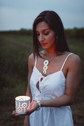 Young woman in nature, holding candle in the evening - MAUF01653