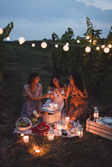 Friends having a picnic in a vineyard on summer night - MAUF01662