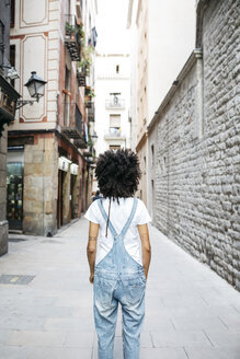 Spain, Barcelona, back view of woman with curly hair wearing dungarees - JRFF01729