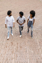 Three friends walking on a square having fun together - JRFF01738