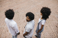Three friends with curly hair standing on a square - JRFF01741