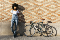 Woman with racing cycle leaning against brick wall - JRFF01747