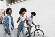 Three friends with racing cycle walking on the street - JRFF01750