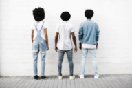 Back view of three friends standing side by side in front of white wall - JRFF01753