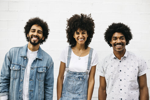 Group picture of three laughing friends in front of white wall - JRFF01759