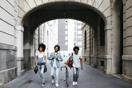 Spain, Barcelona, three friends with racing cycle walking on the street - JRFF01762