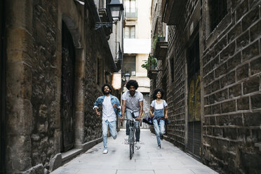Spain, Barcelona, man riding bicycle down an alley while his friends running behind him - JRFF01768