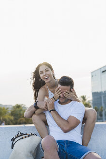 Laughing young woman surprising her boyfriend, covering his eyes - AFVF01176
