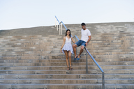 Young couple walking down stair, man sliding on railing - AFVF01188