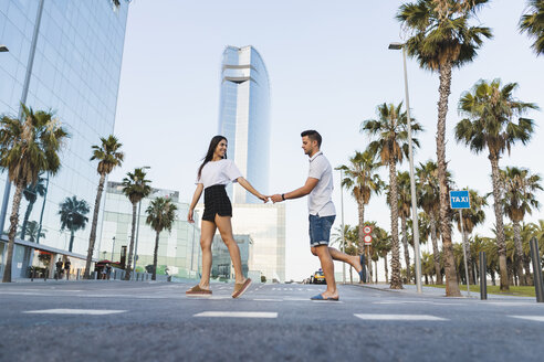Young couple crossing street in the city, holding hands - AFVF01206