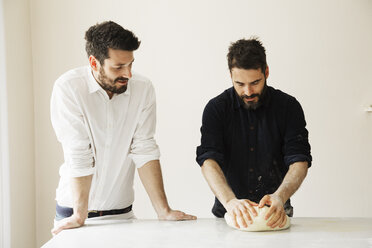 Two bakers standing at a table, kneading bread dough. - MINF03352