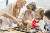 A woman and three children creating a baked gingerbread house. - MINF03421