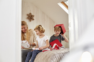 Christmas morning in a family home. A mother and two children sitting on a bed opening presents. - MINF03502