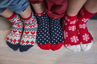 Three pairs of children's feet in bright patterned Christmas socks. - MINF03511