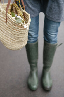 A woman in wellingtons and jeans carrying a basket. - MINF03523