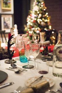 A table laid for a Christmas meal, with silver and crystal glasses and a Christmas tree in the background. - MINF03613