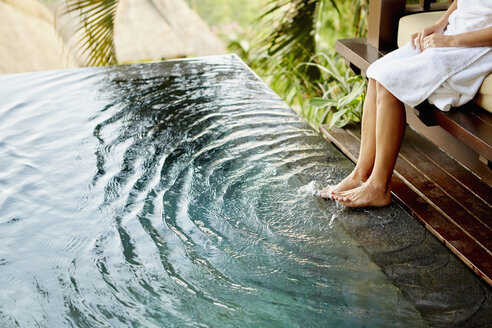 A person sitting on a bench with her feet in the shallow water of a pool, making ripples. - MINF03625