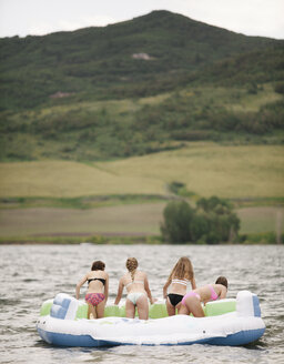 Teenage girls in an inflatable dinghy on a lake. - MINF03808