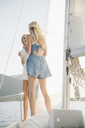 Portrait of two blond sisters on a sail boat. - MINF03880