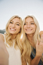 Portrait of two blond sisters on a sail boat. - MINF03889