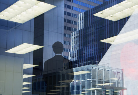 Rear view of man wearing suit standing at window, reflections of recessed office ceiling lights and skyscrapers. - MINF03934
