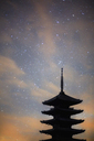 Silhouette of tall wooden pagoda of Buddhist temple against evening sky. - MINF03937