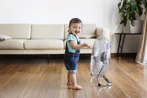 Young boy wearing denim dungarees, standing on hardwood floor in front of electric fan. - MINF04024