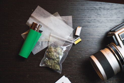 Marihuana, cigarette lighter and analog camera on wood - KKAF01346