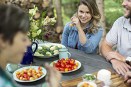 Three people seated at a table outdoors, with fresh fruit and vegetables in plates on the table. - MINF04060
