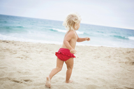 Back view of toddler running on beach - ISF19622