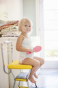 Girl sitting on yellow chair holding hairbrush, portrait - ISF19631