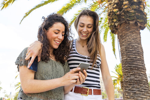 Two happy female friends looking at a smartphone under a palm tree - WPEF00747