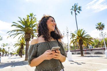 Smiling teenage girl holding smartphone at waterfront promenade - WPEF00750