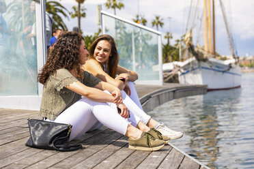Two happy female friends talking at waterfront promenade - WPEF00753