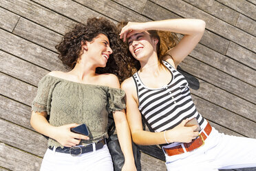 Two happy female friends lying down on a wooden floor - WPEF00756