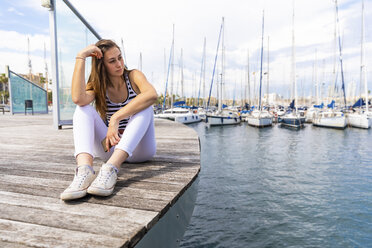 Young woman sitting on promenade at a marina - WPEF00759