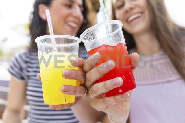 Close-up of two female friends enjoying a fresh slush - WPEF00765