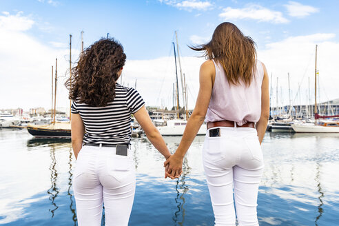 Rear view of two female friends holding hands at a marina - WPEF00771