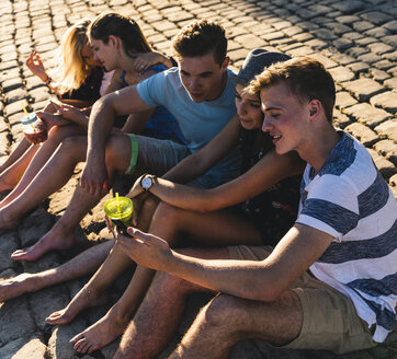 Group of friends sitting on cobblestones with refreshing drinks and cell phones - UUF14808