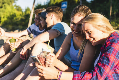 Group of happy friends sitting outdoors with refreshing drinks and cell phones - UUF14811