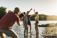 Group of happy friends with tablet in a river at sunset - UUF14814