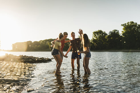 Group of happy friends in a river at sunset - UUF14817