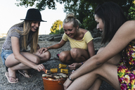 Three young women sitting together having a barbecue - UUF14832