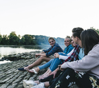 Group of friends sitting at the riverside in the evening - UUF14844