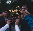 Group of friends holding sparklers in the evening - UUF14850
