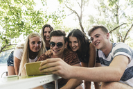 Group of happy friends looking at cell phone outdoors - UUF14859